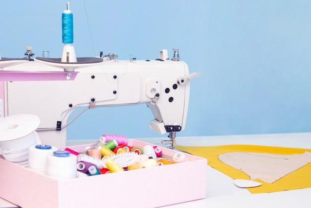 縫製スタジオ。ミシン。裁縫用のアイテムのセット:糸、針、ピン、はさみ、巻尺など