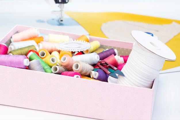 縫製スタジオ。ミシン。裁縫用のアイテムのセット:糸、針、ピン、巻尺など