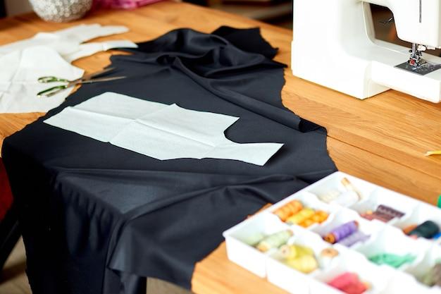 木製のテーブルにミシン用品と機械:ミシン糸、はさみ、布片、針、センチメートル、パターン。