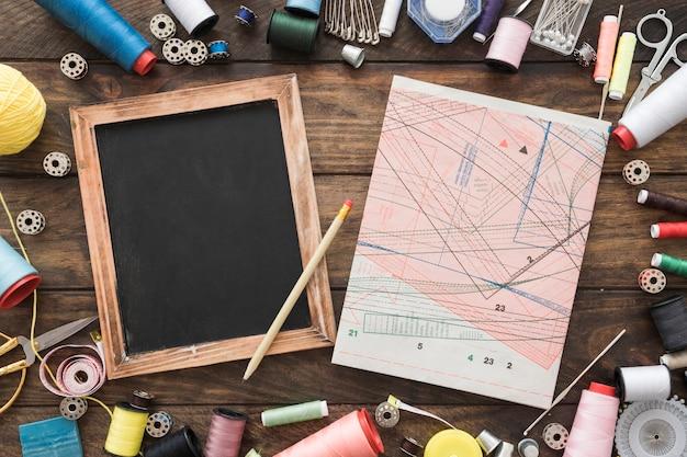 Sewing supplies around pattern and blackboard