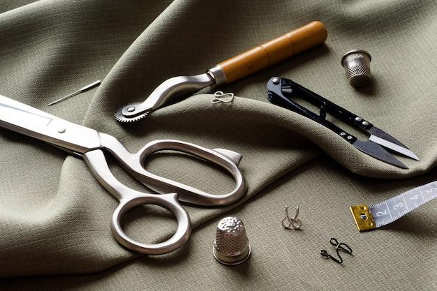 裁縫用品は、ドレープ生地、クローズアップにあります。縫製の背景。灰色のドレープ布の上に、糸のスプール、センチメートル、はさみ、指ぬき。アトリエのコンセプト。ファッションデザイナー。縫製構成。