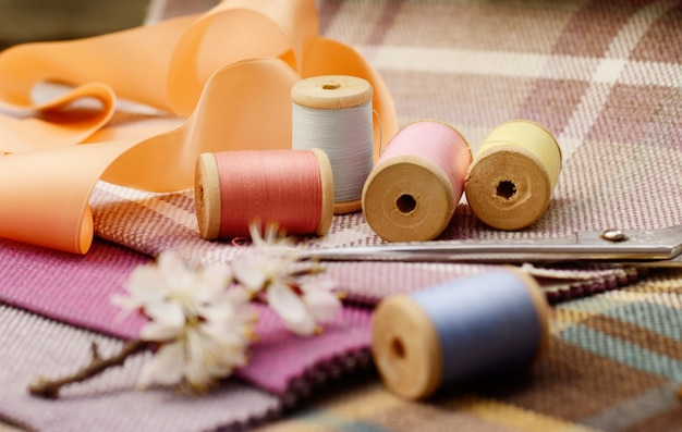 Sewing supplies, needles, scissors on the colorful gunny textile
