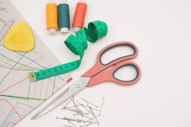 Sewing supplies for needlework, scissors, threads, needles, patterns, chalk, tape for measurement