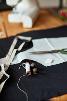 나무 테이블에 바느질 용품 : 바느질 실, 가위, 천 조각, 바늘, 센티미터, 패턴.