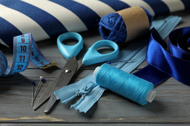Швейные принадлежности на сером деревянном фоне, крупным планом