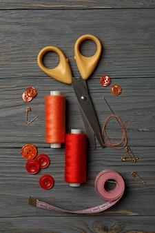 Швейные принадлежности на сером деревянном фоне, вид сверху