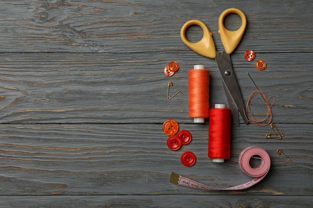 Швейные принадлежности на сером деревянном фоне
