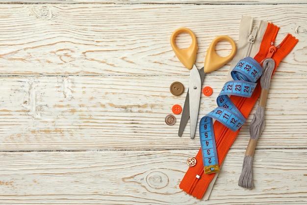 Швейные принадлежности на белом деревянном фоне, место для текста