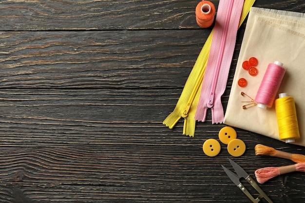 Швейные принадлежности на деревянном фоне вид сверху