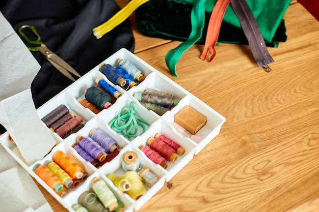 Sewing supplies on a wooden table: sewing thread, scissors, pieces of cloth, needles, centimeter, pattern.