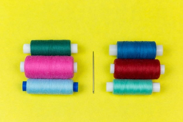 Sewing thread and needle on a yellow background.