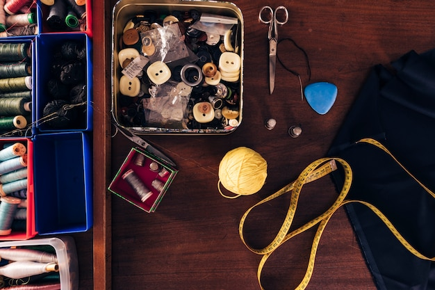 Sewing thread spools; buttons; wool ball; measuring tape; chalk; fabric and scissor on wooden table