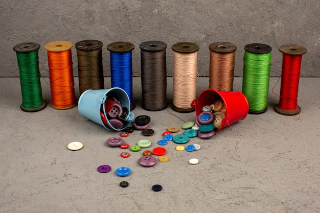 Sewing threads colorful along with mutlicolored plastic vintage buttons on a grey