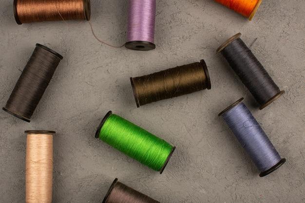 Цветные швейные нитки на сером столе