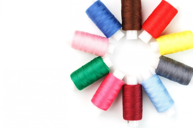 Sewing threads of different colors on reels on white in a circle.