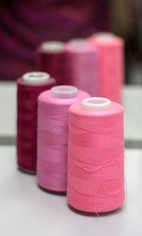 Швейные нитки розовых оттенков на зеркале в ателье.
