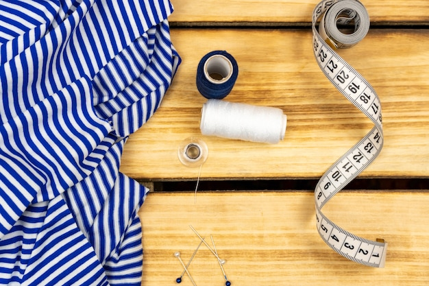 재봉사, 측정 테이프 및 스트라이프 드레스는 나무 재봉 테이블에 있습니다. 절단 및 바느질 개념.