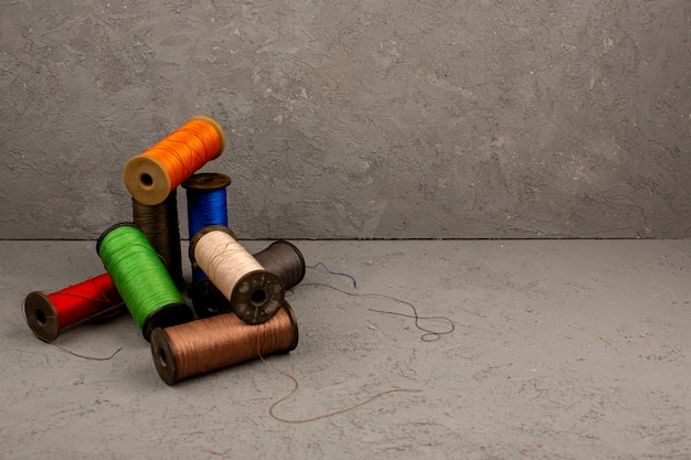 Sewing threads multicolored on a grey desk