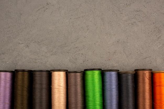 灰色の背景に色とりどりのミシン糸