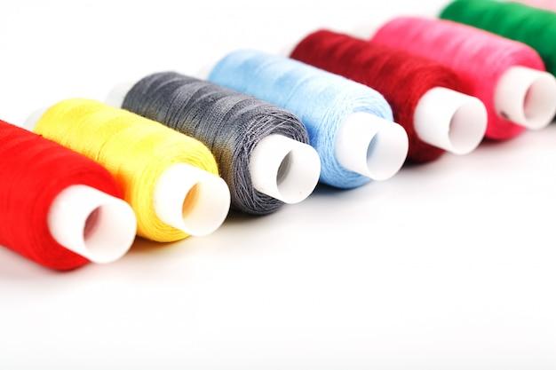 흰색 배경에 릴에 서로 다른 색상의 바느질 스레드