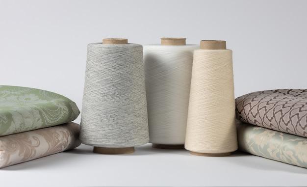 Швейные нитки на деревянных катушках с постельным бельем на белом изолированном фоне