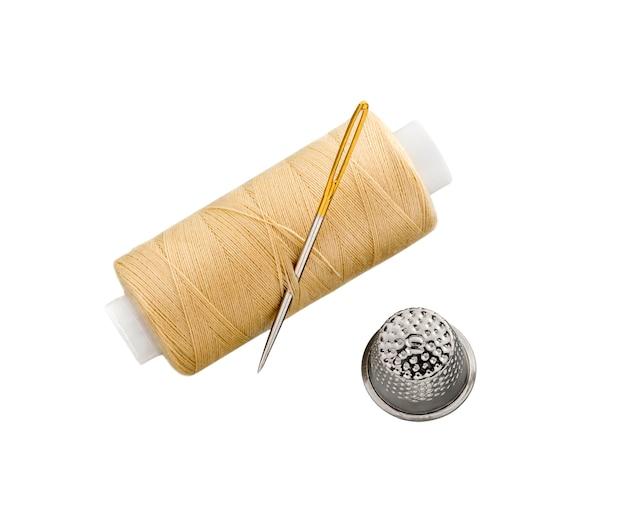 Катушка швейных ниток с швейной иглой и наперстком, изолированные на белом фоне