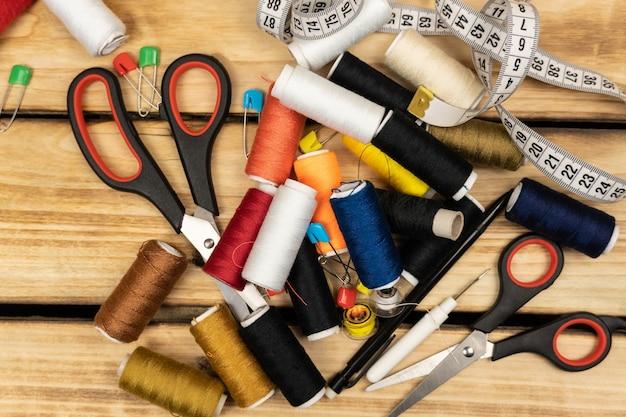 바느질 도구 및 액세서리-컬러 스레드, 스풀, 가위, 핀 및 재단사 미터 나무 배경