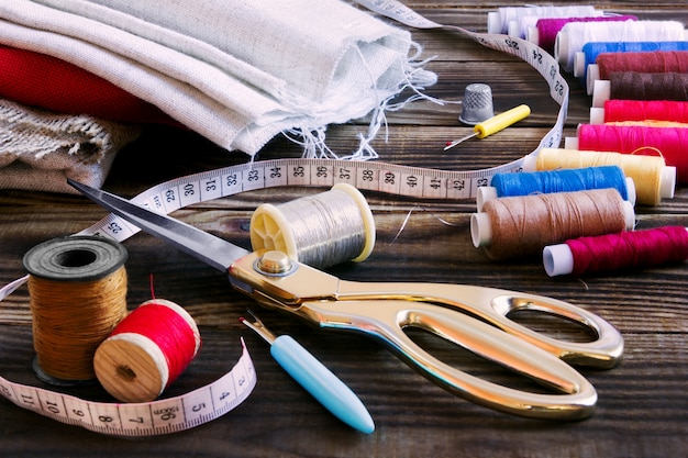 Sewing tools, multi-coloured fabric and threads on a wooden background