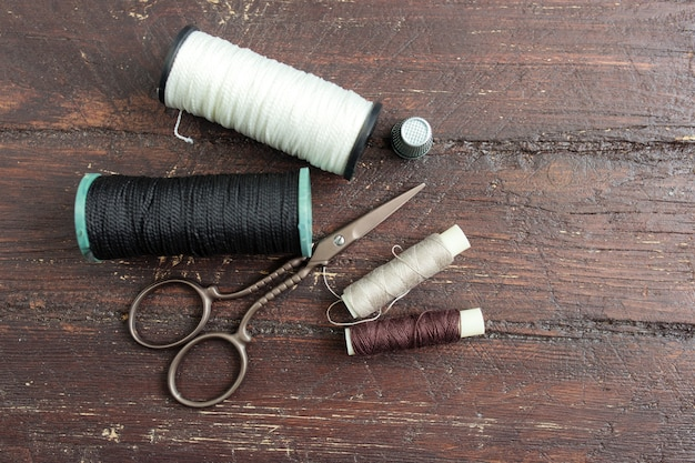 Sewing tools on the old wooden background