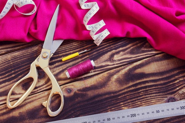 Sewing tools, pink fabric and thread on a wooden background