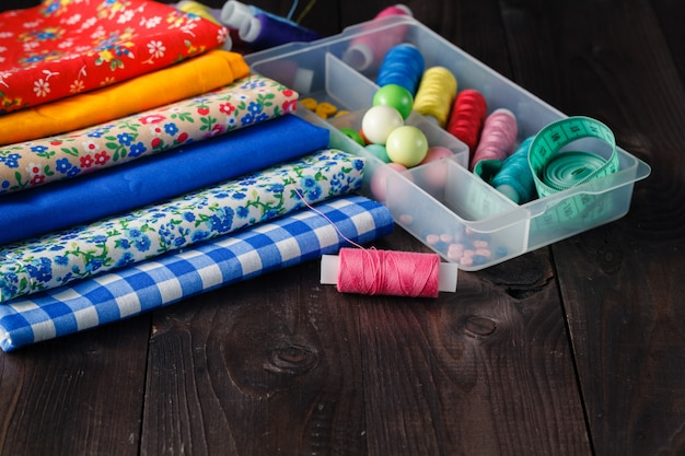 Sewing tools and sewing kit on wooden textured  surface