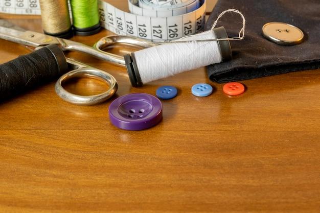 縫製トリム。糸、針、ボタン、はさみ、巻尺のスプール。
