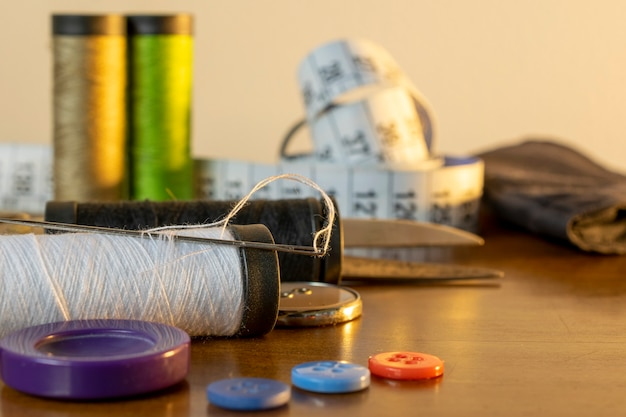 Sewing trims. spool of thread, needle, buttons, scissors and measuring tape.