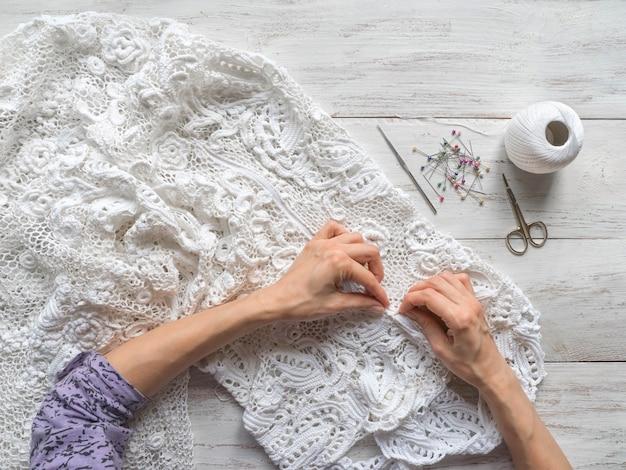 アイリッシュレースのウェディングドレスを縫います。 Premium写真