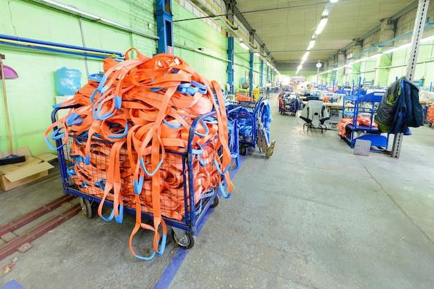 Швейный цех по производству нейлоновых пуховых лямок. контейнер из металлической сетки с оранжевыми мягкими грузовыми стропами.