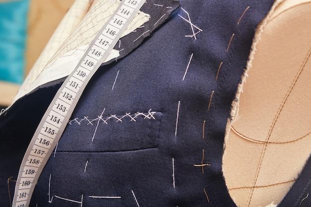 セミレディのスーツジャケットに胸ポケットを縫い付けました。カスタムメイドのジャケットの工程でのスーツの仕立て。テーラーワークショップでのオーダーメイドのスーツテーラリング。オーダーメードのスーツジャケットに取り組んでいます