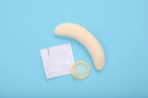 Sex education with banana and condom isolated on blue background