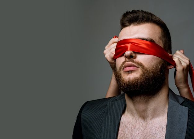 Sex game. tease and seduce. passionate lovers. sex domination and submission. awakening his desire. female tease guy. macho well groomed bearded hipster tied eyes red ribbon. sexual relations.