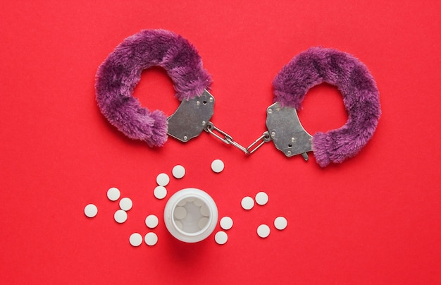 Sex stimulation. handcuffs for sex games with pills on red background. sexual bdsm toy. fetish, erotic concept. top view