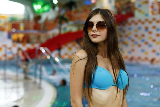 The sexual girl stands near swimming pool