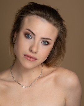 Sexual girl with heterochromia, nose piercing and plug in one ear, and strange hairstyle. she has amazing professional makeup and silver chain around her neck. beige background. studio shot
