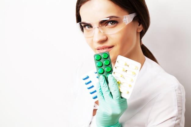 성 건강, 남성의 건강한 성생활을 위해 알약을 들고 흰 코트를 입은 의사.