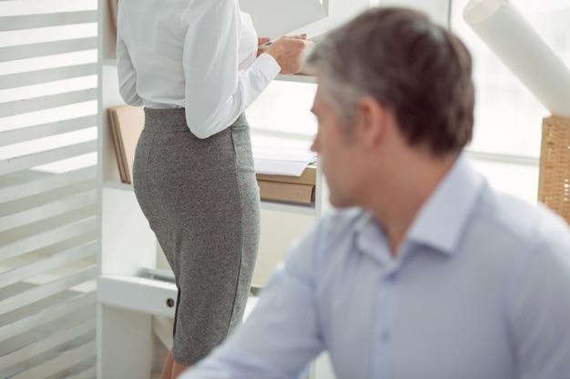 성적 관심. 사무실에 서서 보면서 일하는 매력적인 좋은 젊은 여자