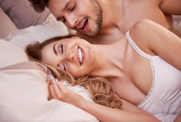 Сексуальная сцена страстной молодой пары в спальне
