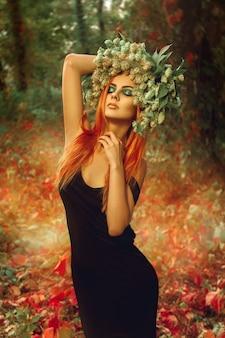 屋外でポーズをとって森の中で頭にホップの花輪を持つ性的なスリムな女性
