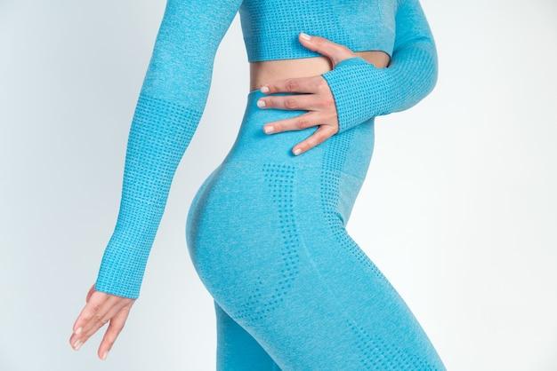 파란색 스포츠 옷을 입고 프로필에 서서 흰색 배경에 대해 포즈를 취하는 성적 슬림 여성. 매력적인 날씬한 여성이 그녀의 완벽한 몸매를 보여줍니다. 웰빙 개념