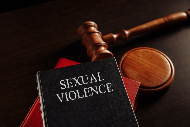 Sexual violence concept. wooden gavel on the big red book.