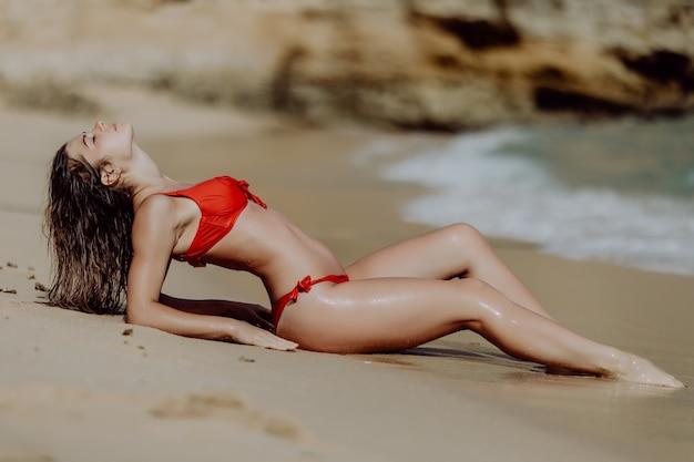 La donna sessuale prende il sole sulla spiaggia.