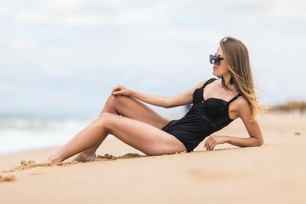 Сексуальная молодая девушка принимает солнечные ванны, лежа на песке на пляже, в стильных купальных костюмах.