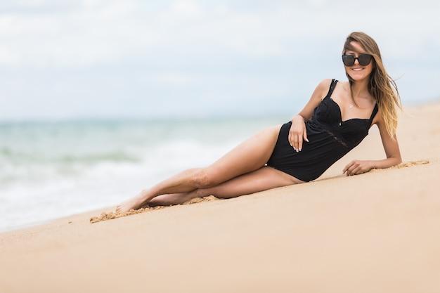 性的な若い女の子は、スタイリッシュな水着を着てビーチの砂の上に横たわって日光浴をします。